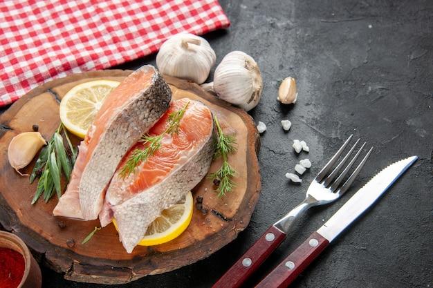 Vista frontal de fatias de peixe fresco com fatias de limão, alho e temperos em carne escura, prato de frutos do mar, foto de alimentos crus