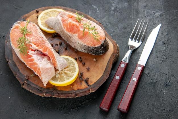 Vista frontal de fatias de peixe fresco com limão e talheres em um prato escuro com fotos de carnes e frutos do mar