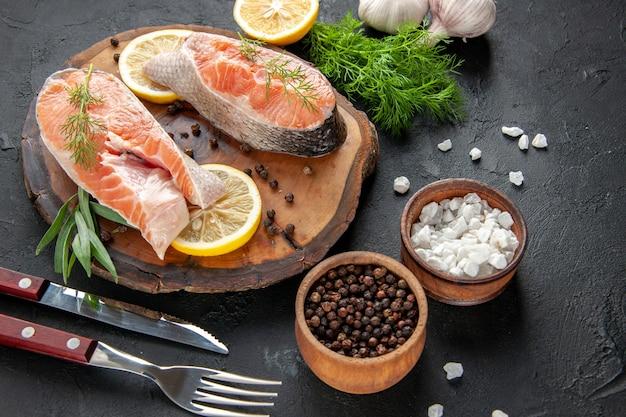 Vista frontal de fatias de peixe fresco com rodelas de limão e alho na cor escura