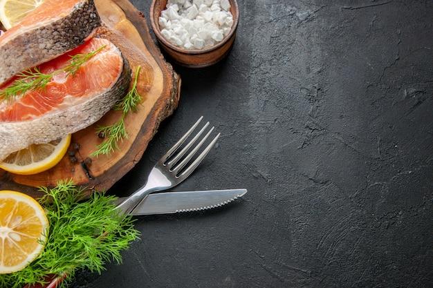 Vista frontal de fatias de peixe fresco com rodelas de limão em um prato de frutos do mar de cor escura, comida, foto de carne crua