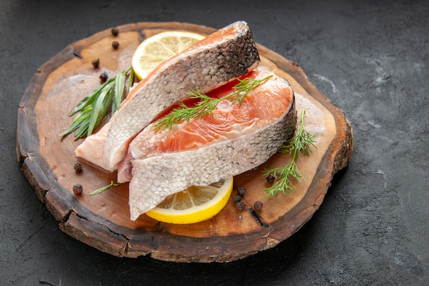 Vista frontal de fatias de peixe fresco com rodelas de limão na cor escura do prato comida, carne, frutos do mar, foto crua