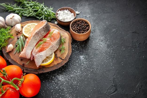 Vista frontal de fatias de peixe fresco com tomate e fatias de limão em um prato de frutos do mar de cor escura com comida crua