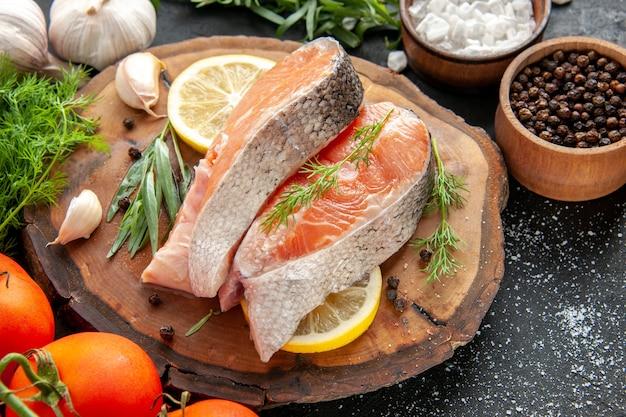 Vista frontal de fatias de peixe fresco com tomate e rodelas de limão em um prato de frutos do mar de cor escura e crua.