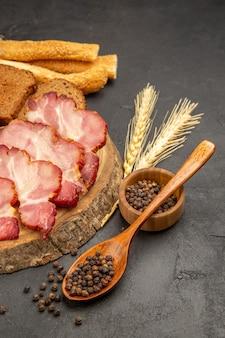 Vista frontal de fatias de presunto com pãezinhos e fatias de pão na refeição de carne de lanche em cor escura
