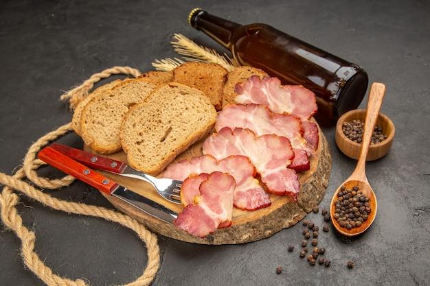 Vista frontal de fatias de presunto fresco com garrafa e fatias de pão na refeição de comida de cor de carne de lanche em foto escura