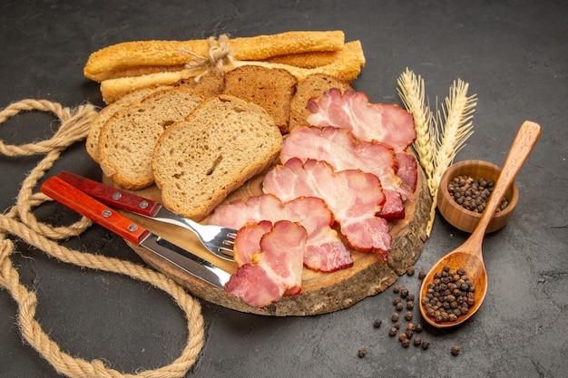 Vista frontal de fatias de presunto fresco com pãezinhos e fatias de pão em refeição de carne de lanche em cor escura