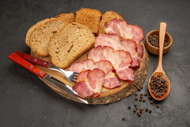 Vista frontal de fatias de presunto fresco com pãezinhos e fatias de pão na refeição com foto a cores de salgadinhos escuros