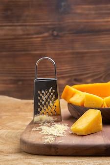 Vista frontal de fatias de queijo em um ralador de tigela na tábua de cortar na superfície de madeira