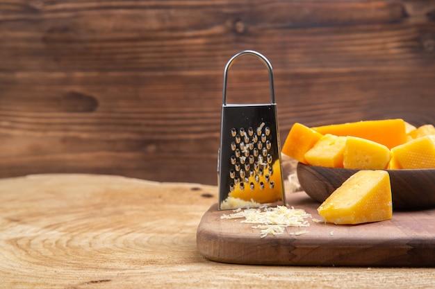 Vista frontal de fatias de queijo em uma tigela de madeira ralador na tábua de cortar na superfície de madeira