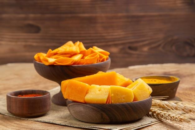 Vista frontal de fatias de queijo em uma tigela pimenta vermelha em pó chips espigão de trigo no jornal em superfície isolada