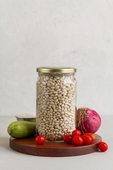 Vista frontal de feijão cru em pote com vegetais