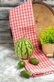 Vista frontal de feijoa verde fresca com melancia em fundo cinza, fruta de cor verde suave