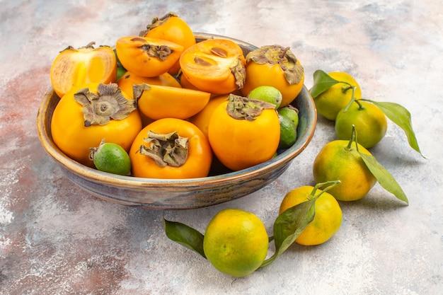 Vista frontal de feijoas de caquis frescos em uma tigela e tangerinas em fundo nude