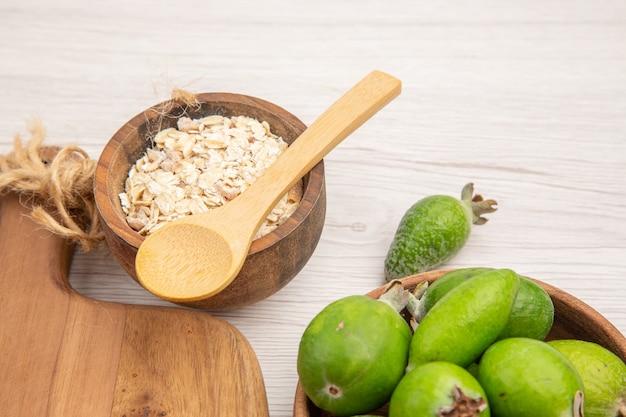 Vista frontal de feijoas frescas com cereais em fundo branco tropical cor madura dieta exótica suave