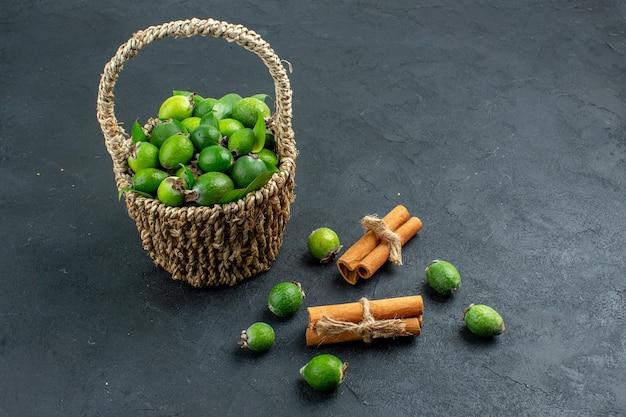 Vista frontal de feijoas frescas em uma cesta em bastões de canela na superfície escura