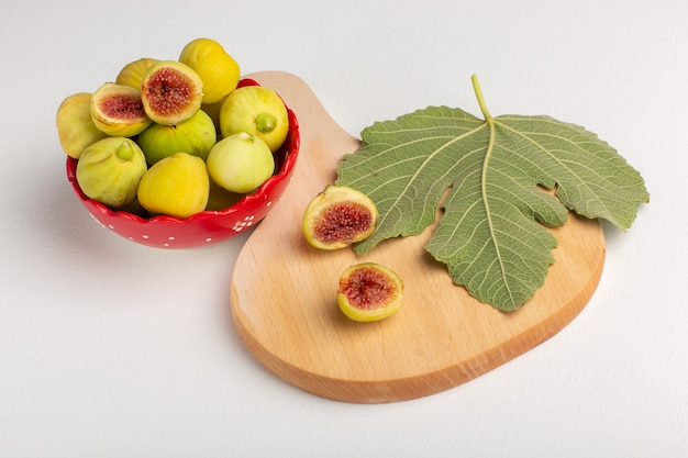 Vista frontal de figos doces frescos deliciosos fetos dentro de uma placa vermelha na mesa branca