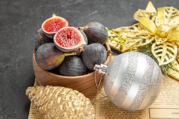 Vista frontal de figos frescos com brinquedos de árvore de natal em fundo escuro árvore de frescor de foto de frutas