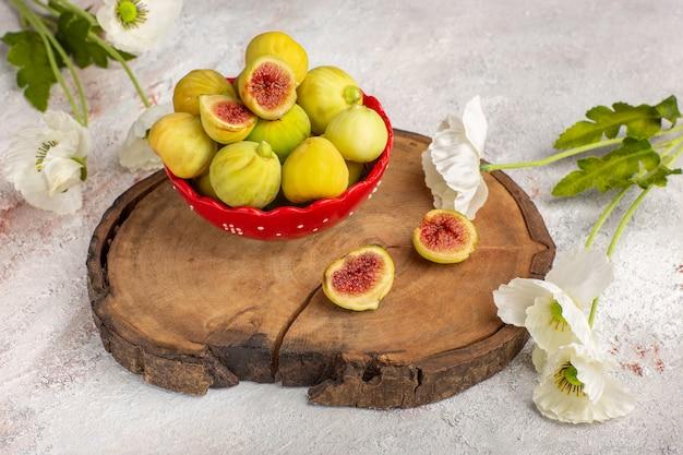 Vista frontal de figos frescos e doces deliciosos fetos dentro de um prato vermelho com flores na mesa branca