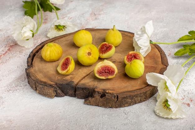 Vista frontal de figos frescos e doces deliciosos fetos em uma mesa marrom