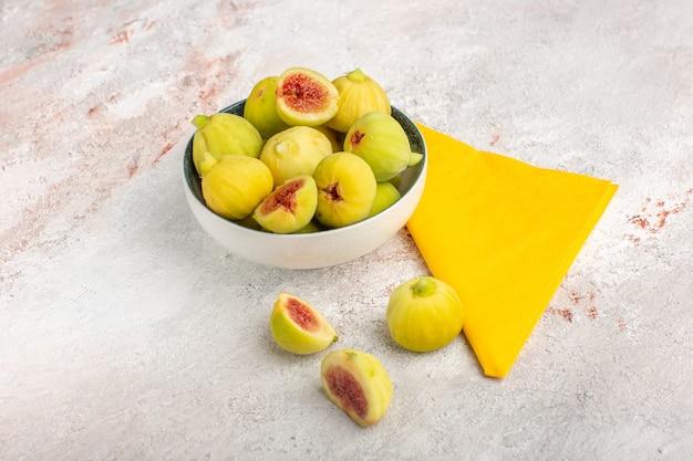 Vista frontal de figos frescos e fetos doces dentro de um prato na mesa branca