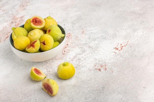 Vista frontal de figos frescos, fetos doces dentro do prato na superfície branca clara