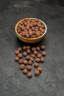 Vista frontal de flocos de chocolate em fundo escuro refeição com leite café da manhã cacau