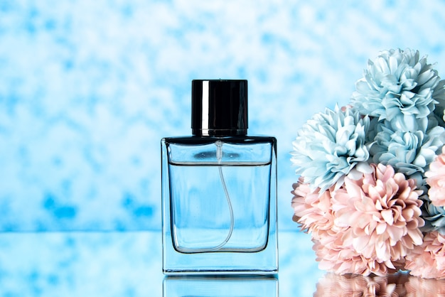 Vista frontal de flores coloridas de perfume elegante em fundo azul claro