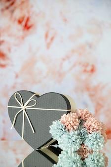 Vista frontal de flores coloridas em caixa de coração preto em fundo bege desfocado