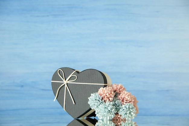 Vista frontal de flores em caixa colorida em forma de coração preto em azul com local de cópia