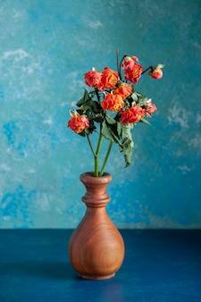 Vista frontal de flores vermelhas murchas dentro de um vaso na superfície azul