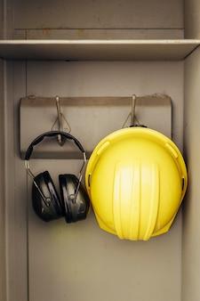 Vista frontal de fones de ouvido e capacete pendurados em um armário