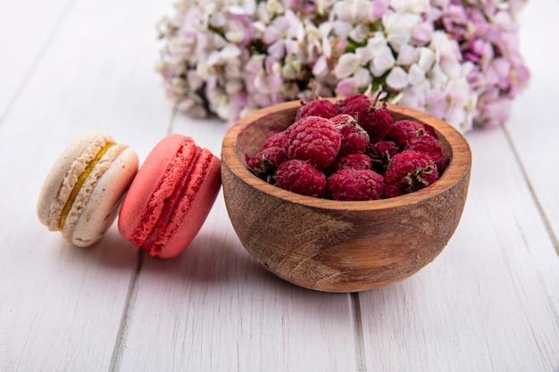 Vista frontal de framboesas em uma tigela com macarons e um buquê de flores em uma superfície branca