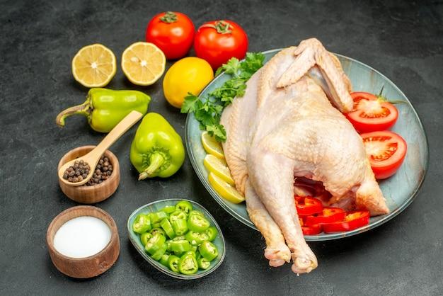Vista frontal de frango cru fresco com tomate, limão e verduras no fundo escuro foto de refeição madura de salada de carne