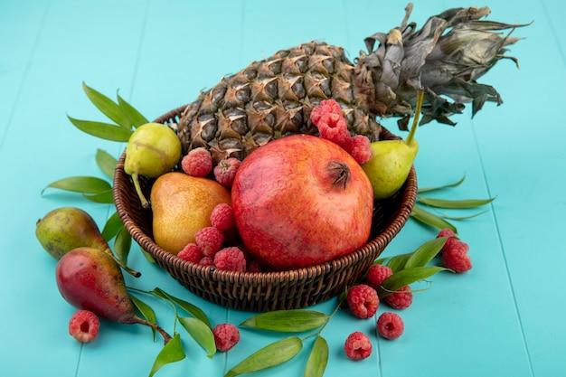 Vista frontal de frutas como abacaxi romã pêssego framboesa na cesta com folhas na superfície azul