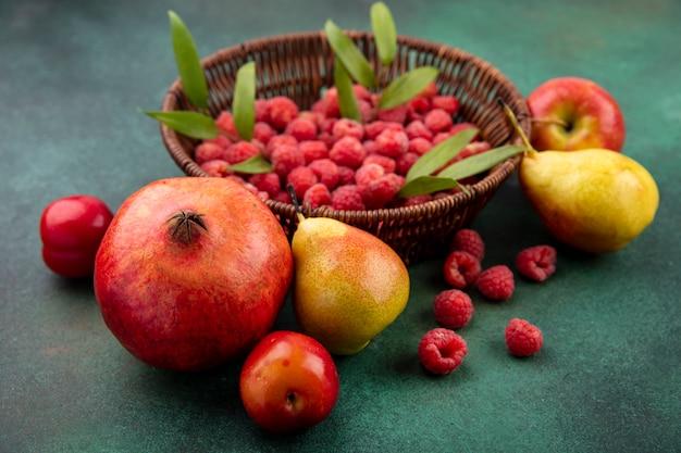Vista frontal de frutas como ameixa de romã pêssego com cesto de framboesa na superfície verde