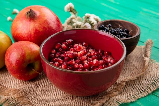Vista frontal de frutas como bagas de romã e abrunheiro em taças com flores de saco e maçãs de romã na superfície de saco e verde