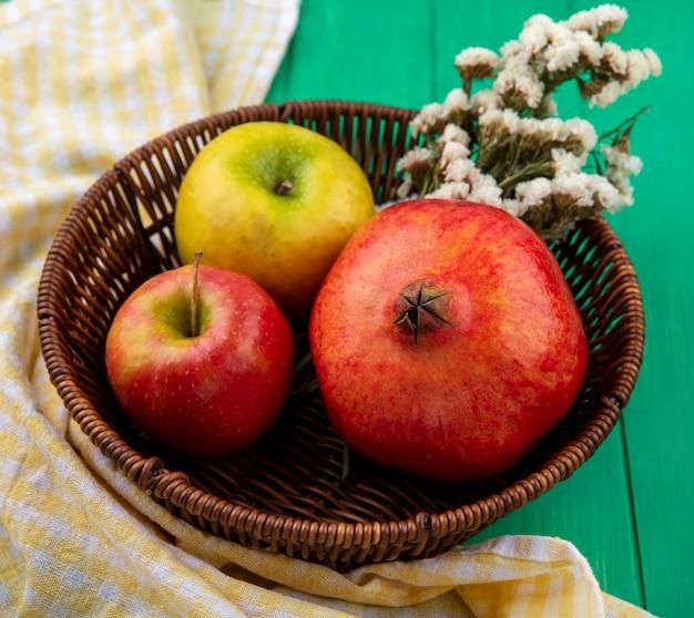 Vista frontal de frutas como maçã e romã com flores na cesta no pano xadrez e superfície verde