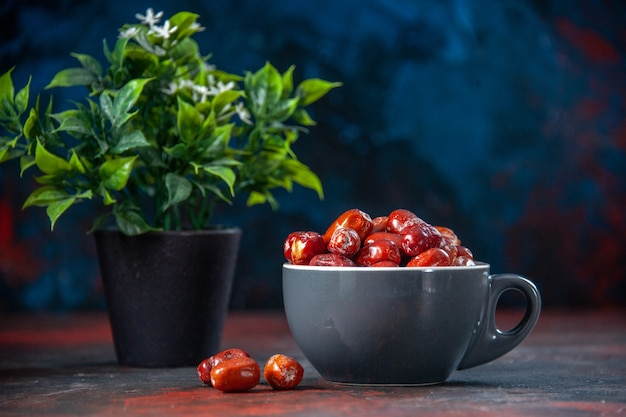 Vista frontal de frutas frescas de amora-prateada, dentro e fora de um copo cinza e um vaso de flores no fundo de cores misturadas com espaço livre