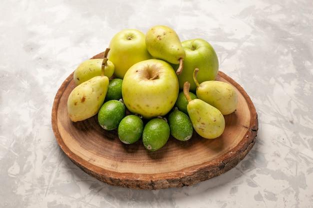Vista frontal de frutas frescas, maçãs, feijoa e peras no espaço em branco