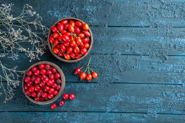 Vista frontal de frutas vermelhas frescas dentro de pratos em uma mesa de madeira escura.