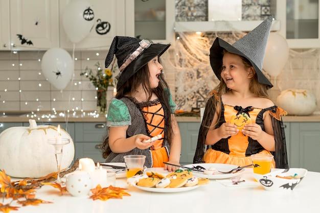 Vista frontal de garotas felizes fantasiadas de bruxa