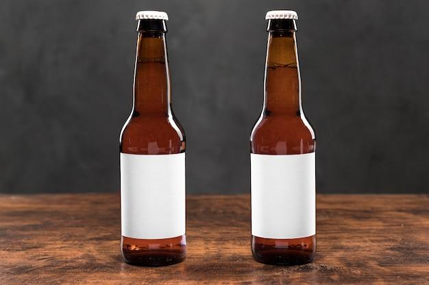 Vista frontal de garrafas de cerveja com adesivos em branco na mesa
