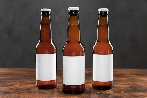 Vista frontal de garrafas de cerveja com adesivos em branco