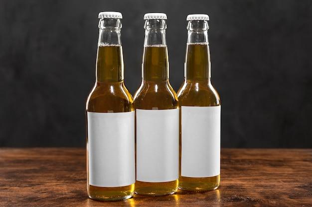 Vista frontal de garrafas de cerveja com rótulos em branco na mesa
