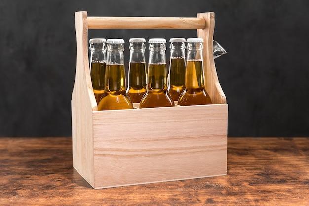 Vista frontal de garrafas de cerveja em caixa de madeira