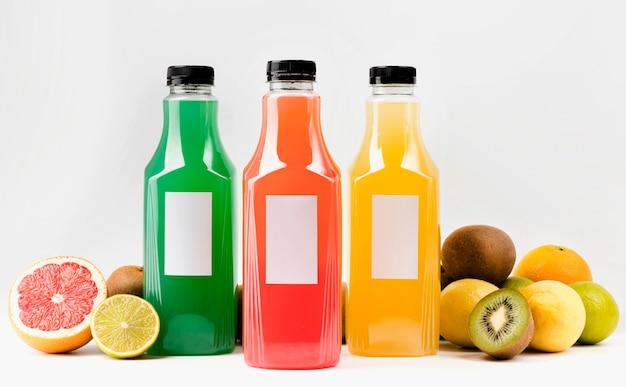 Vista frontal de garrafas de suco coloridas com tampas e frutas