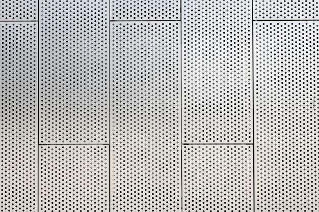 Vista frontal de grades metálicas e furos redondos na superfície metálica