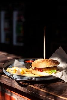 Vista frontal de hambúrguer no prato com batatas fritas e espaço de cópia