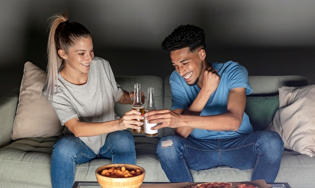 Vista frontal de homem e mulher brindando com cerveja em casa enquanto assiste tv