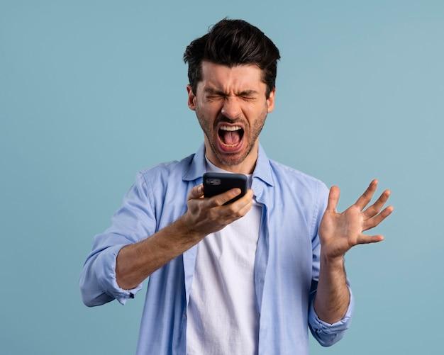 Vista frontal de homem gritando com smartphone
